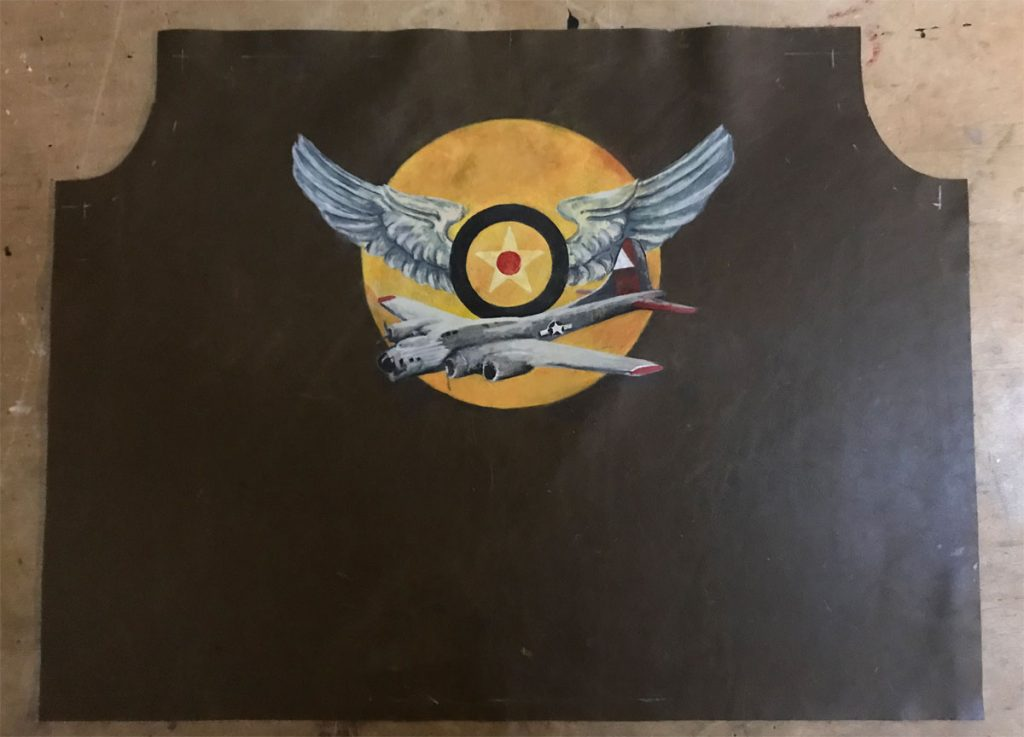 Wing and airplane graphic painted on jacket back just prior to jacket assembly