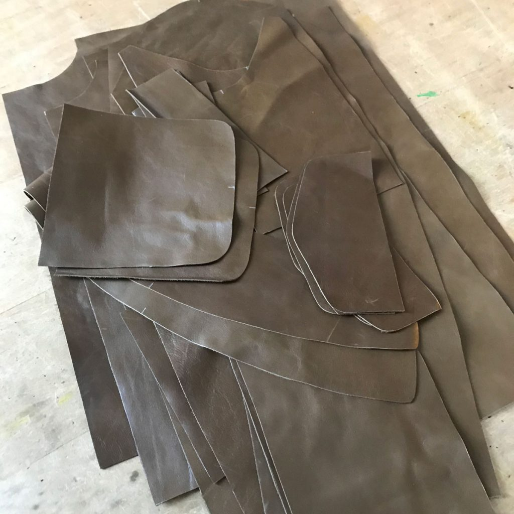 A jacket's worth of pieces cut from 2.5oz cowhide and stacked on the worktable
