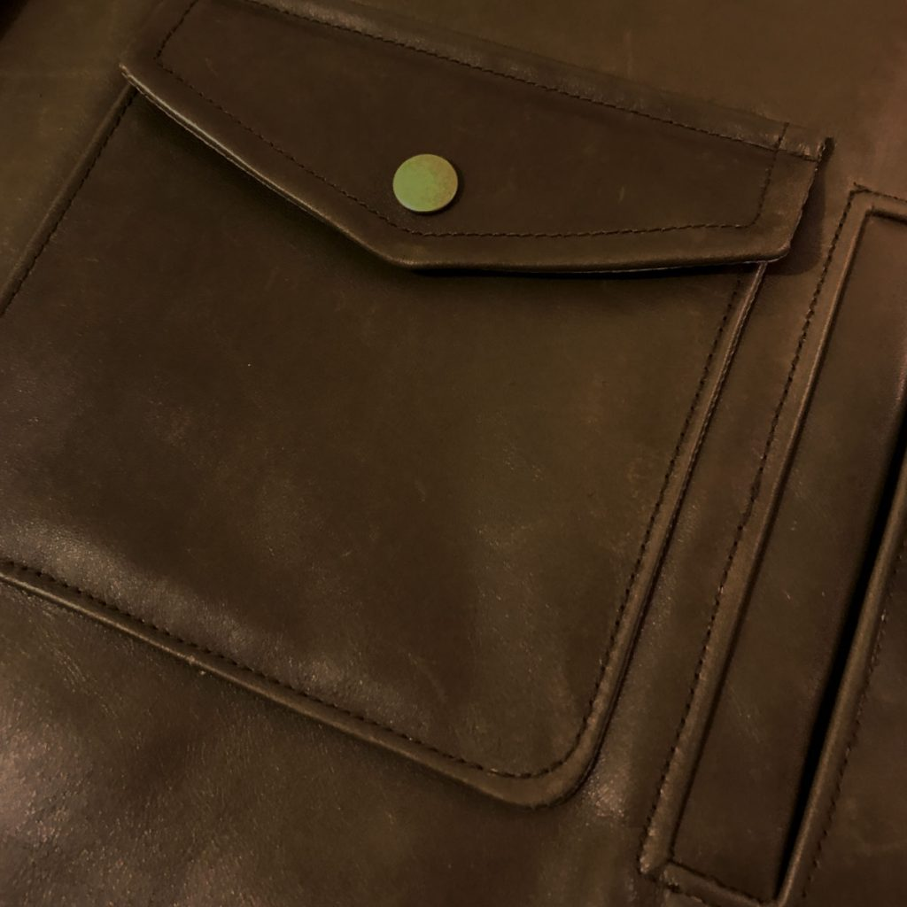 Close-up of a patch pocket with pointed flap and snap closure, with a single-welt pocket opening next to it