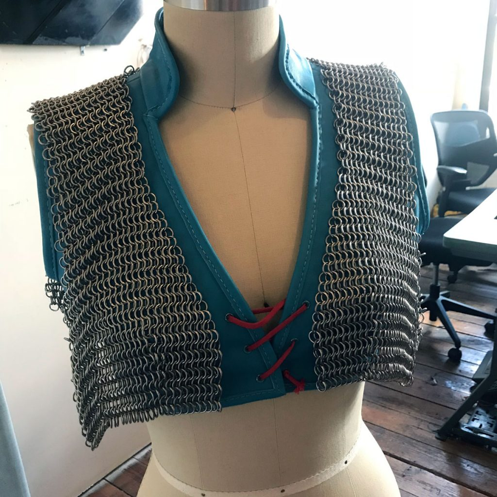 Chainmail vest loosely draped over leather vest on dress form