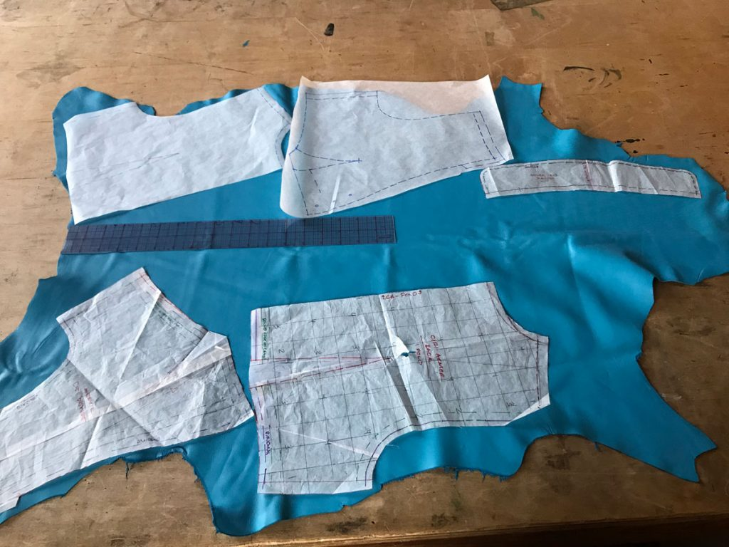 vest pattern pieces laid out on blue lambskin