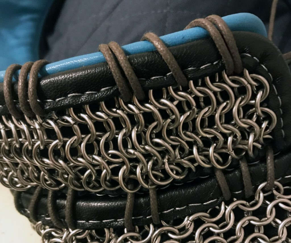 Blue leather and chainmail vests laced together with cotton cord around the edges