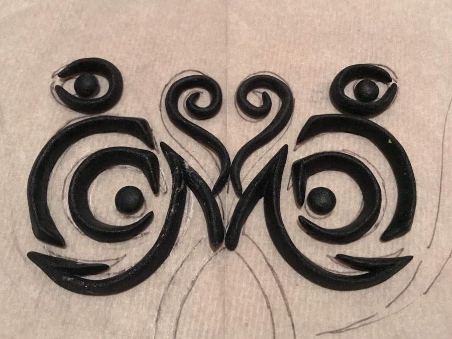 individually sculpted details arranged on top of hand-drawn paper pattern