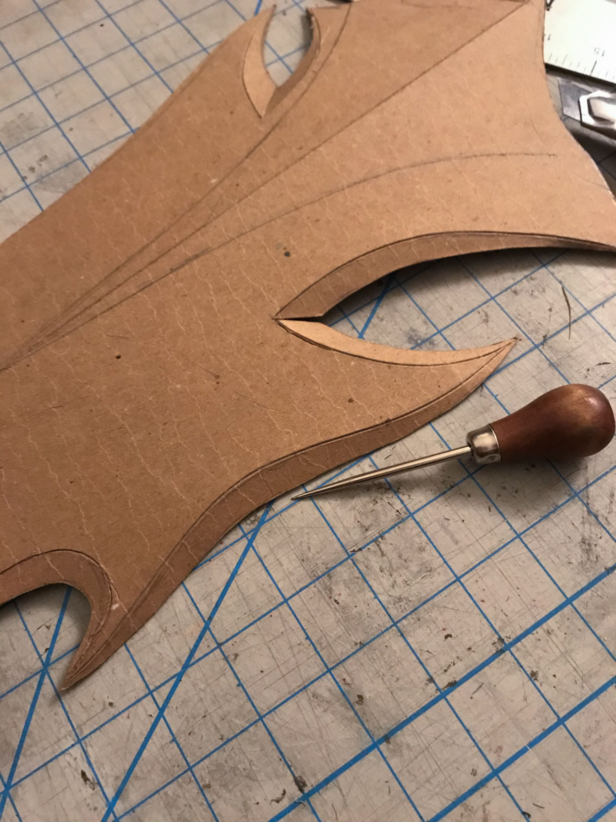 awl and cardboard sword base with scored fold lines